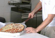 Un trabajador de un restaurante especializado en pizza